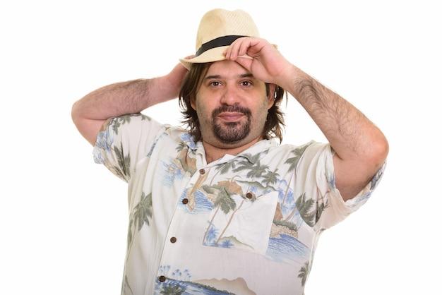 Dikke blanke man tot vaststelling van hoed klaar voor vakantie geïsoleerd op wit