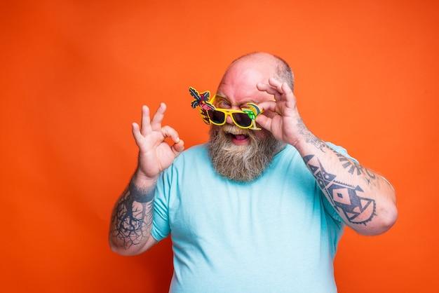 Dikke blije man met baardtattoos en zonnebril is klaar voor de zomer