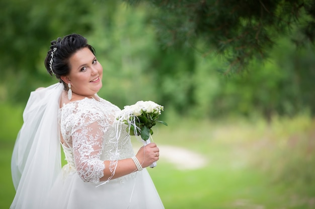 Dikke bruid met een bruiloft boeket op een zomerse achtergrond.