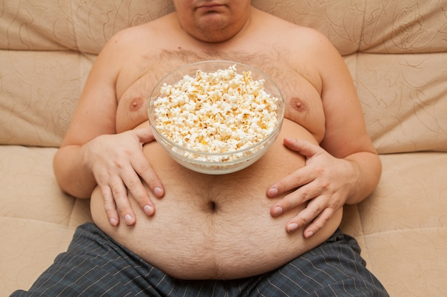 Dikke buik van een zwaarlijvige man. de gevolgen van ondervoeding