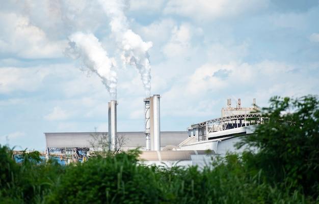 Dikke en zware rook komt uit een enorme, witte rook komt uit schoorstenen of uitlaatpijpen in de fabrieksschoorstenen stoten waterdamp uit die condenseert tot een witachtige wolk voordat deze verdampt.