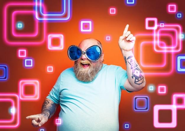Dikke gelukkige man met baardtattoos en zonnebril danst muziek