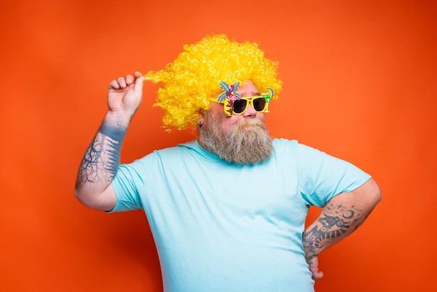 Dikke gelukkige man met baardtattoos en zonnebril heeft plezier met de gele pruik