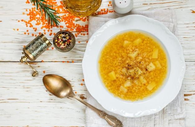 Dikke hete linzensoep met aardappelen en kruiden in een witte plaat