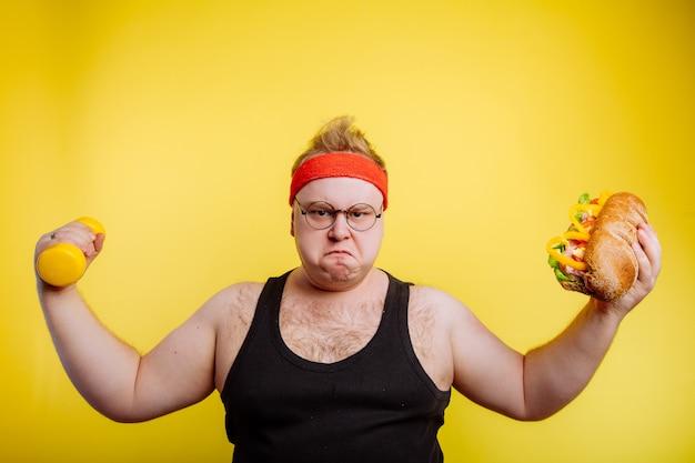 Dikke hongerige man toont biceps met hamburger en halter