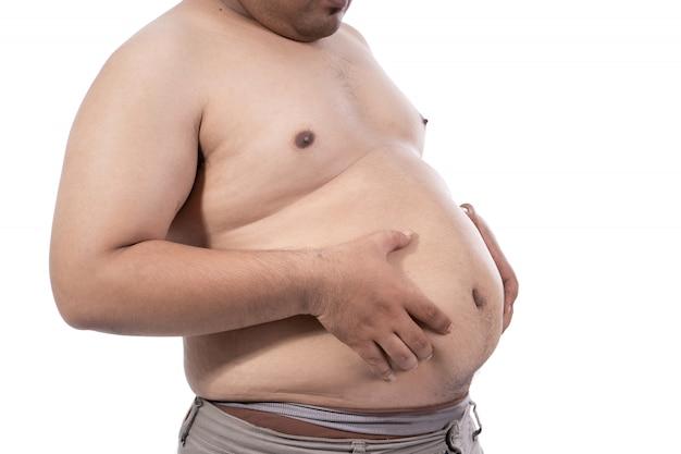 Dikke jonge man knijpt overtollig vet rond zijn middel