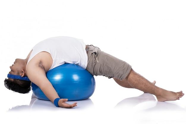 Dikke jonge mannen doen pilates met ontspannen liggen