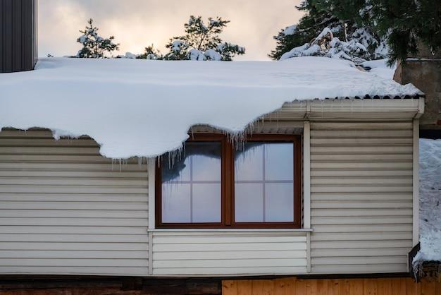Dikke laag sneeuw die van de rand van het dak hangt.