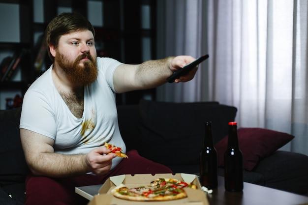Dikke man eet pizza zittend op de bank en schakelt van kanaal op de tv