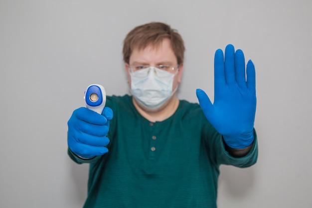 Dikke man in een masker en handschoenen met een thermometer zegt stop