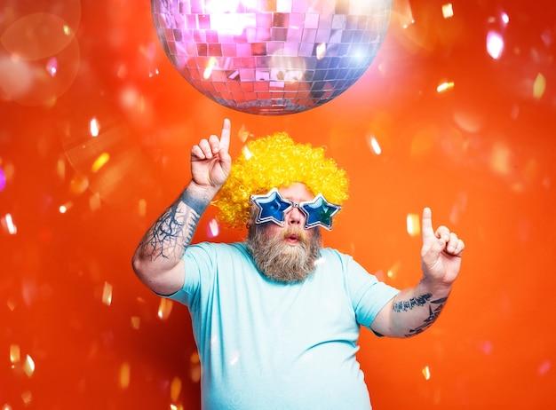 Dikke man met baardtatoeages en zonnebril danst muziek in een disco