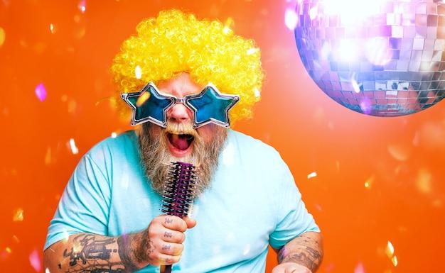 Dikke man met baardtattoos en zonnebril zingt een lied
