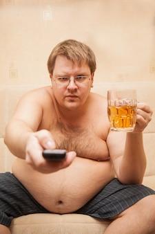 Dikke man met bierbuik voor tv eet popcorn en drinkt bier