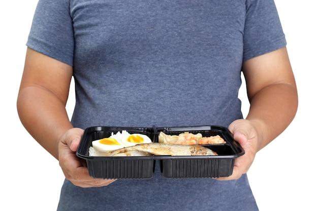 Dikke man met een doos voedsel op een witte achtergrond. concept van gewichtsverlies, gezond eten, eten bestellen tijdens de coronavirusepidemie. uitknippad