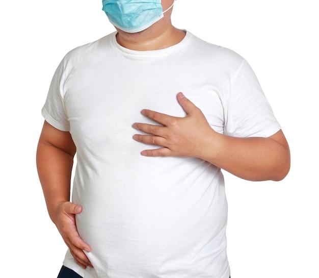 Dikke man met een masker pijn op de borst, moeite met ademhalen loopt het risico diabetes te ontwikkelen hypertensie coronaire hartziekte hyperlipidemie het risico op coronavirus. witte achtergrond. uitknippad