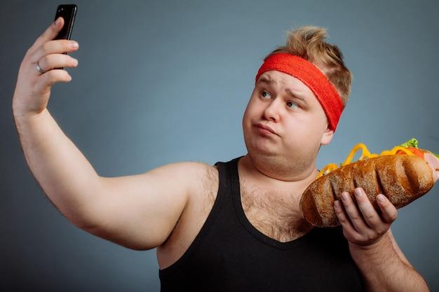Dikke man met sandwich in de hand maakt selfie