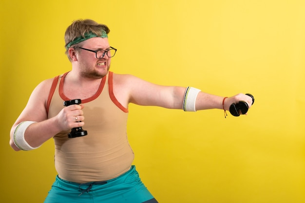 Dikke man met zwarte shirt trainen met halters en camera kijken.