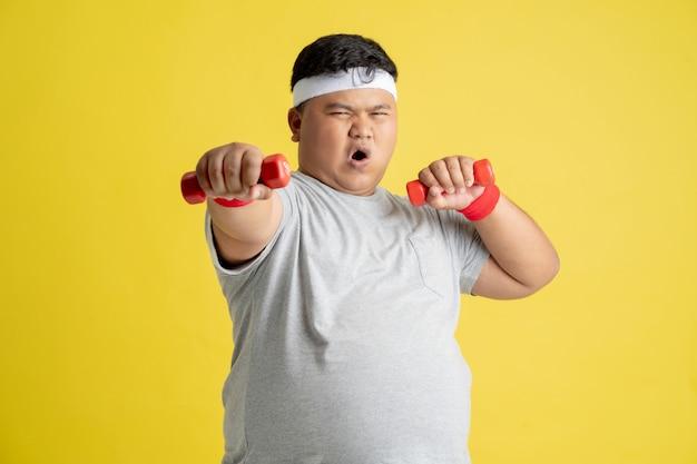 Dikke man oefent door gewichten op te heffen