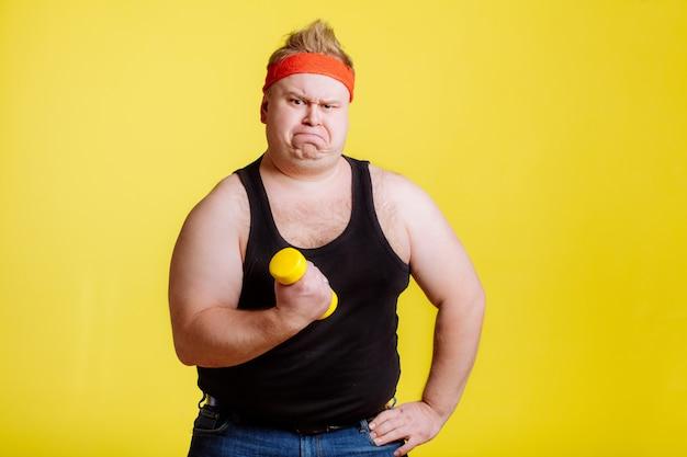 Dikke man probeert kleine gele dumbell op te tillen
