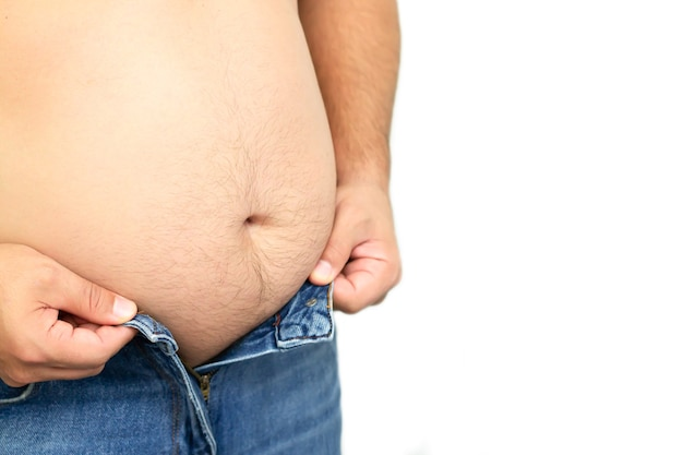 Dikke man probeert zijn jeans broek knop dicht te knopen vanwege zijn dikke buik geïsoleerd op een witte achtergrond.