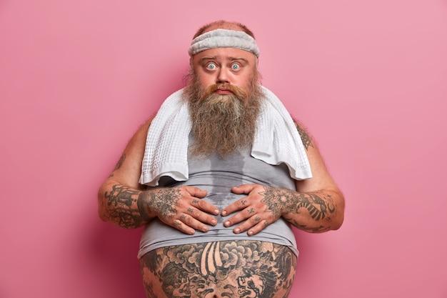 Dikke man raakt dikke buik aan, heeft zweetlichaam, werkt hard aan gewichtsverlies en afslanken, neemt pauze na cardiotraining, draagt sportkleding, poseert tegen roze muur. sport, zwaarlijvigheidsconcept