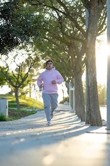 Dikke man rent over het trottoir in een park met zonsonderganglicht erachter
