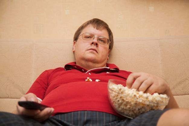 Dikke man tv kijken die popcorn eet