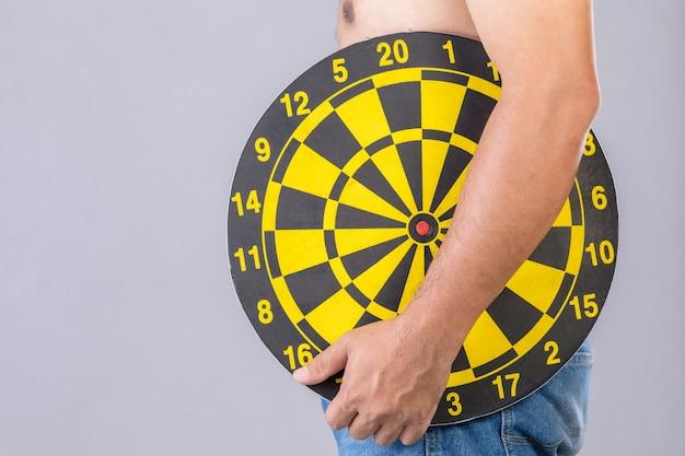 Dikke mensen houden rond geel dartbord naast zijn buikpositie. doelwit van afvallen concept.