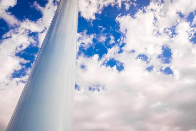 Dikke metalen witte pijp in verticale positie als basis van een toren, geïsoleerd op blauwe hemelachtergrond.