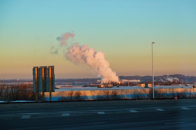 Dikke rook van thermische centrales boven de woonwijken van de stad.