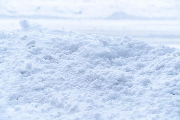 Dikke stapel witte zachte sneeuw bedekt betonnen muur