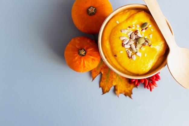Dikke vegan pompoenroomsoep met zaden in een wegwerpbeker. soep voor onderweg, bezorging van gezond eten.