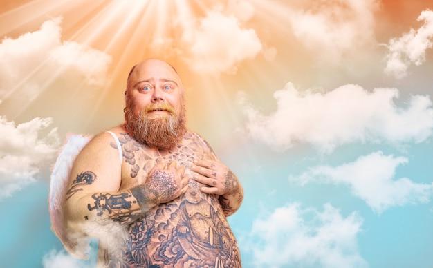 Dikke verbaasde man met baardtatoeages en vleugels gedraagt zich als een engel