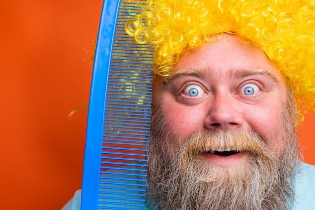 Dikke verbaasde man met baardtatoeages en zonnebril kamt zichzelf met een gigantische kam