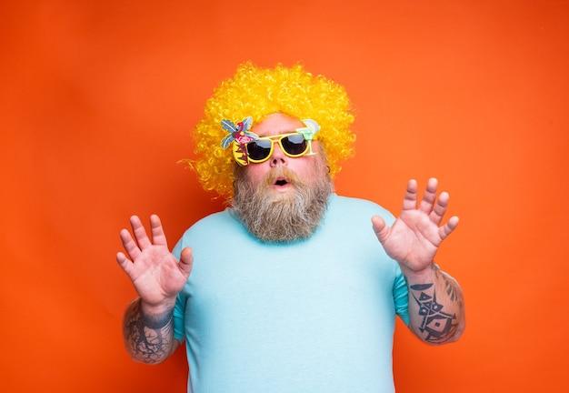 Dikke verbaasde man met baardtattoos en zonnebril heeft plezier met de gele pruik