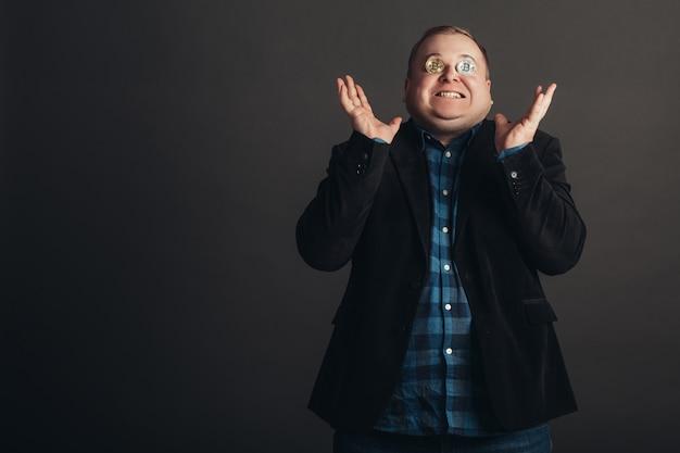Dikke vierende man maakt een gek gezicht. gekke bitcoin-liefhebber met gouden munt op zijn ogen