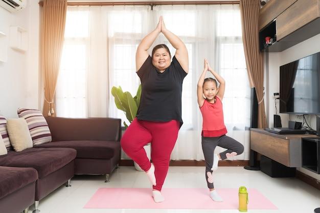 Dikke vrouw aziatisch met meisje die thuis traint, sport en recreatie idee concept.
