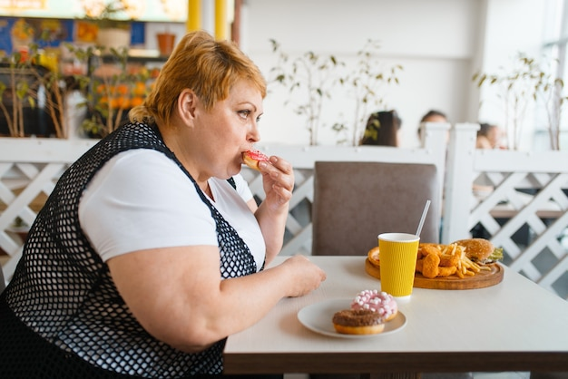 Dikke vrouw die donuts eet in fastfoodrestaurant, ongezond voedsel. vrouwelijke persoon met overgewicht aan tafel met junk-diner, obesitasprobleem