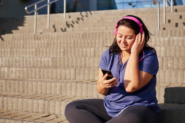 Dikke vrouw die naar muziek luistert via een koptelefoon