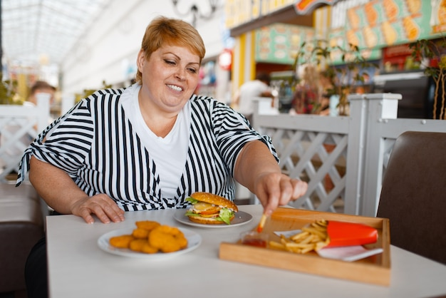 Dikke vrouw frietjes eten in winkelcentrum food court.