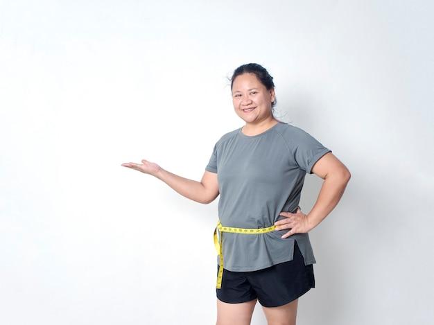 Dikke vrouw taille meten met tape op witte achtergrond met kopie ruimte