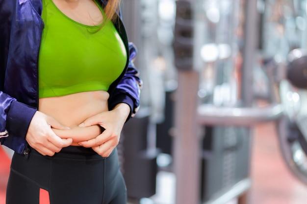 Dikke vrouw, zwaarlijvige vrouw hand met overmatig buikvet, overgewicht vette buik van vrouw, vrouw dieet levensstijl concept om buik te verminderen en gezonde buikspier vorm te geven.