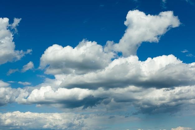 Dikke witte wolken vormen zich in een diepblauwe lucht.