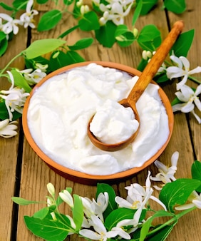 Dikke yoghurt in een aarden kom met lepel en witte bloemen van kamperfoelie