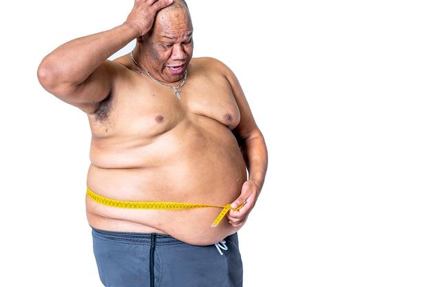 Dikke zwarte dieetman meet zijn verbaasde taille met een meetlint om te zien of hij gewicht heeft verloren met het regime. concept voor gezondheid en obesitas