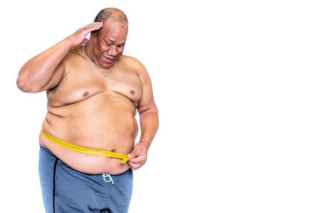 Dikke zwarte man meet zijn bezorgde taille met een meetlint om te zien of hij gewicht heeft verloren met het regime. concept voor gezondheid en obesitas