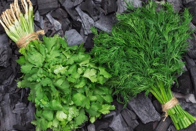 Dille en koriander op houtskool. biologische gezonde voeding. plat leggen