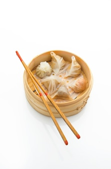 Dim bedragen in een bamboestoomboot met eetstokjes op witte achtergrond