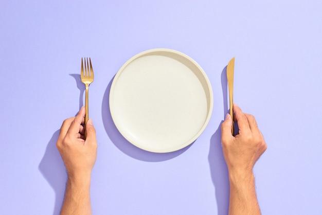 Diner couvert. witte lege plaat en hand met gouden vork en mes op sering