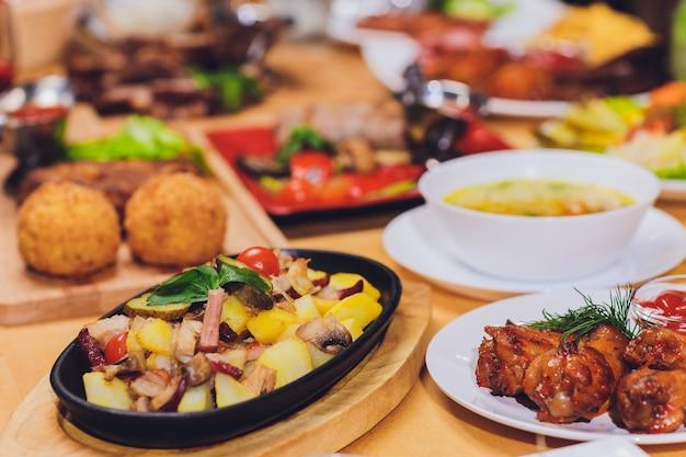 Diner eten concept. eettafel met gegrilde worst, tortilla wraps, bierdrank en verschillende gerechten op houten tafel, rustieke stijl.